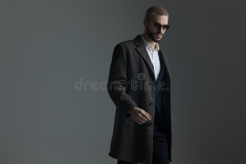 Hombre rubio en traje con las gafas de sol y caminar del longcoat imagen de archivo