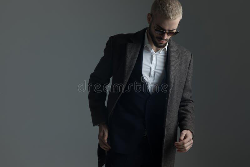 Hombre rubio en traje que camina con la cabeza abajo fotografía de archivo libre de regalías
