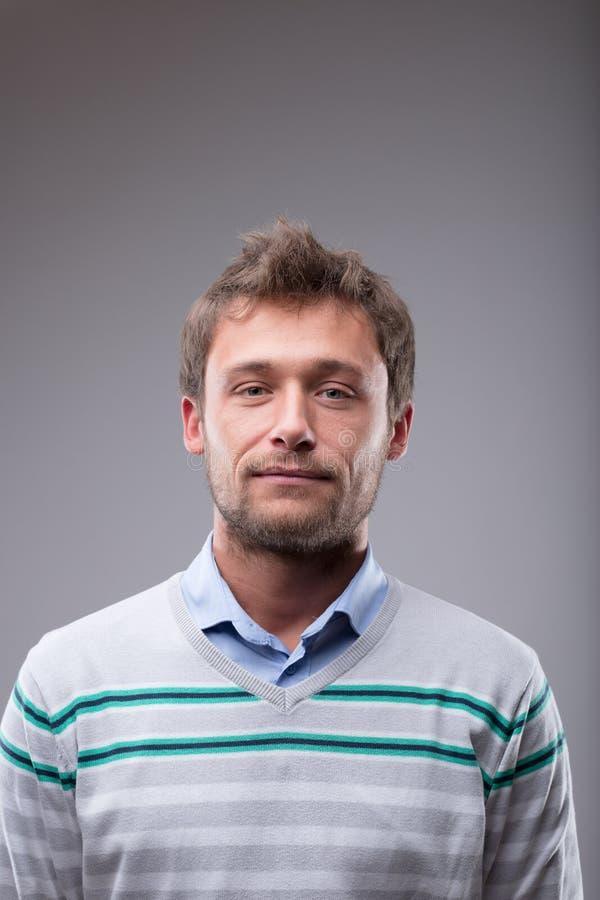 Hombre rubio joven atractivo sobre gris foto de archivo libre de regalías