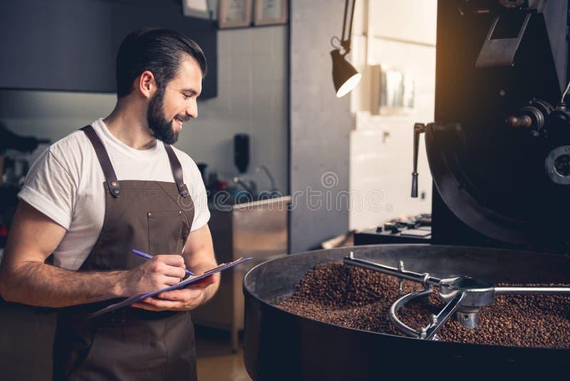 Hombre saliente que observa sobre la preparación de los granos de café foto de archivo
