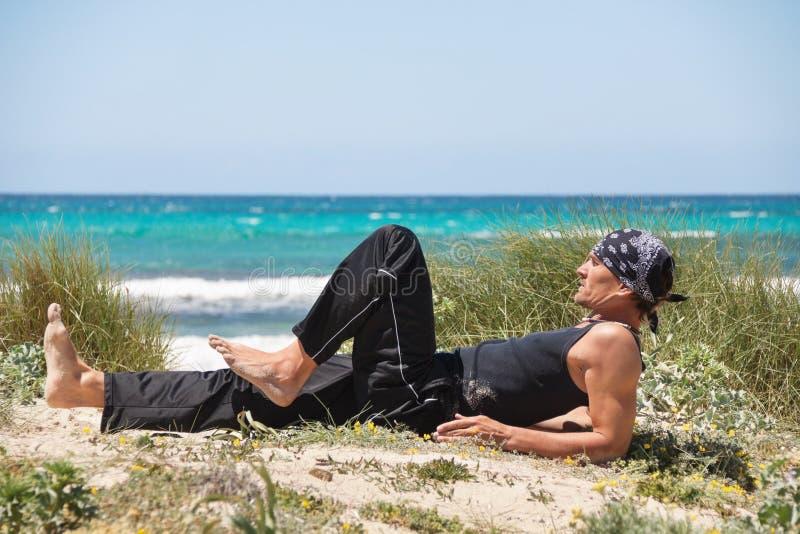 Hombre sano adulto que hace ejercicio de la yoga de los pilates fotos de archivo