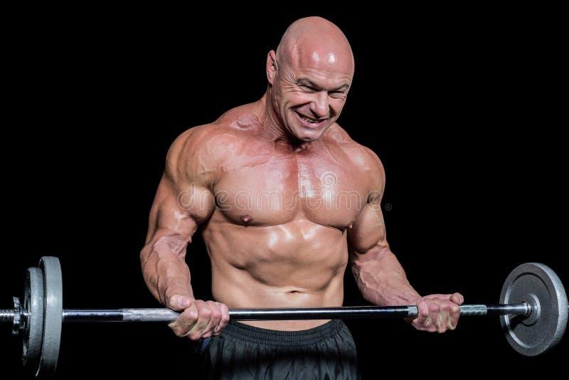 Hombre sano apasionado que ejercita mientras que levanta el crossfit imagen de archivo