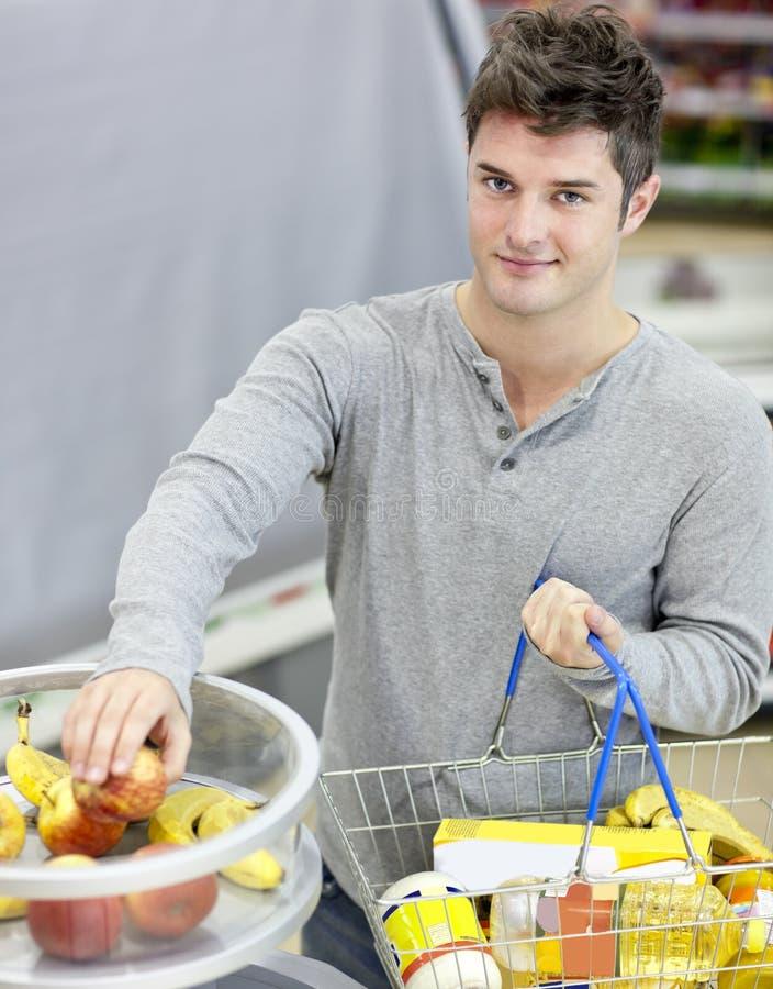 Hombre sano con las frutas de compra de la compra-cesta imagenes de archivo