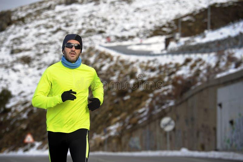 Hombre sano del deporte que corre en el camino en las montañas de la nieve en entrenamiento duro del corredor del rastro en invie imágenes de archivo libres de regalías