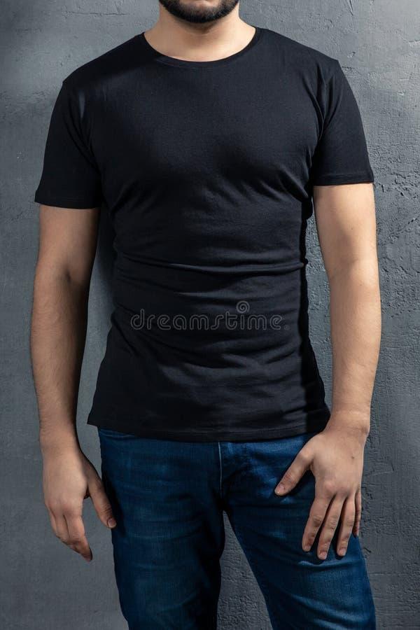 Hombre sano joven con la camiseta negra en fondo concreto imagen de archivo