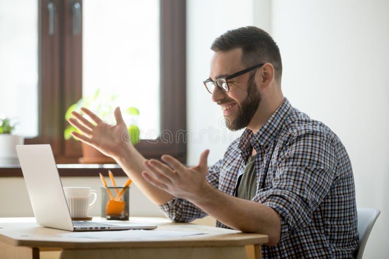 Hombre satisfecho feliz videochatting en su ordenador portátil foto de archivo libre de regalías