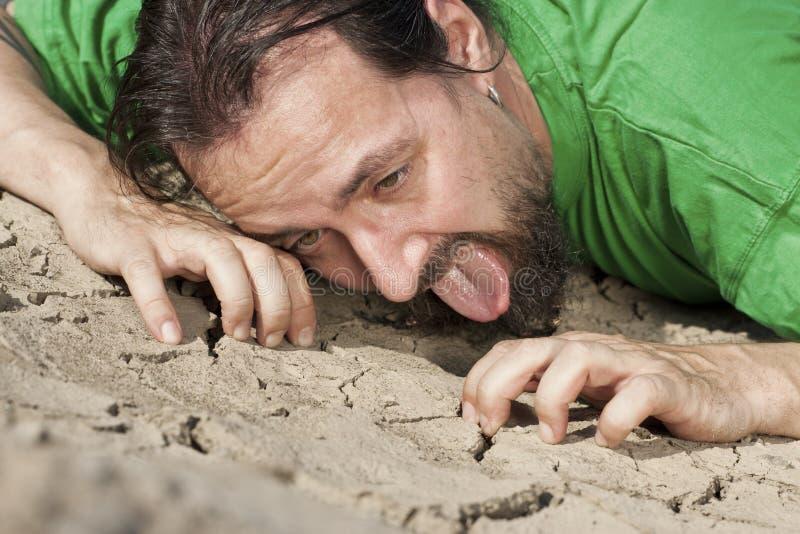 Hombre sediento en suelo secado foto de archivo