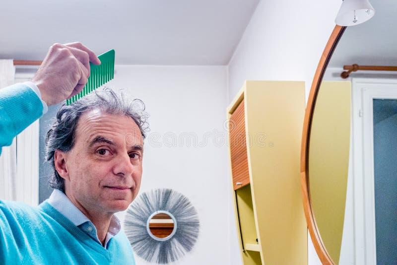 Hombre semicalvo que se peina el pelo foto de archivo libre de regalías