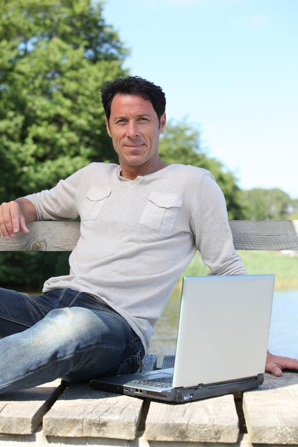 Hombre sentado en banco de parque imagenes de archivo