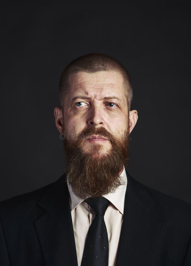 Hombre serio, barbudo en la camisa blanca y obra clásica, chaqueta elegante en fondo oscuro fotografía de archivo