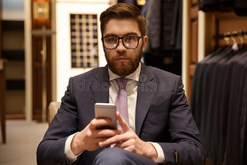 Hombre serio en el traje y las lentes que sostienen el teléfono móvil imágenes de archivo libres de regalías