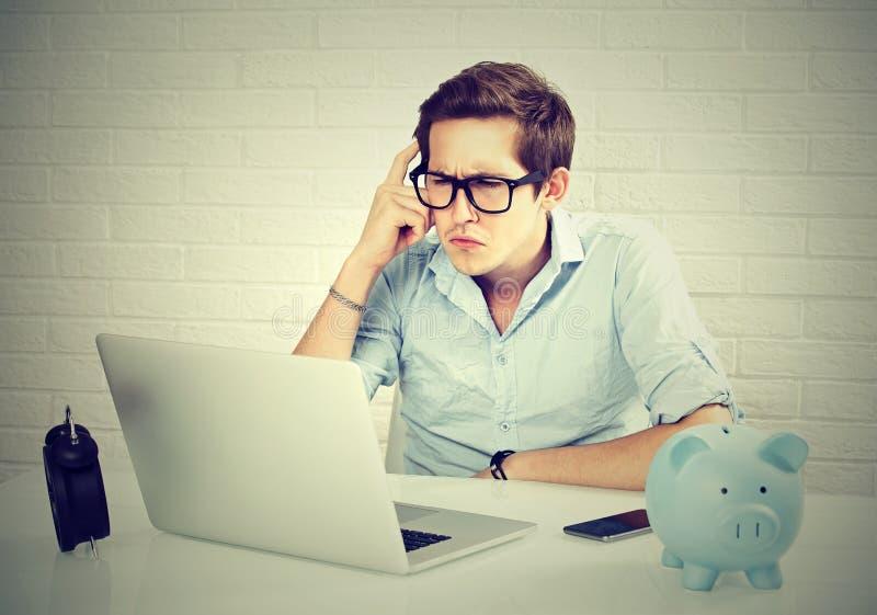 Hombre serio en la camisa azul que mira el ordenador portátil mientras que se sienta en su lugar de trabajo fotos de archivo libres de regalías