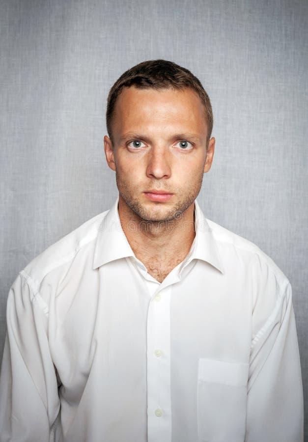 Hombre serio joven en la camisa blanca foto de archivo