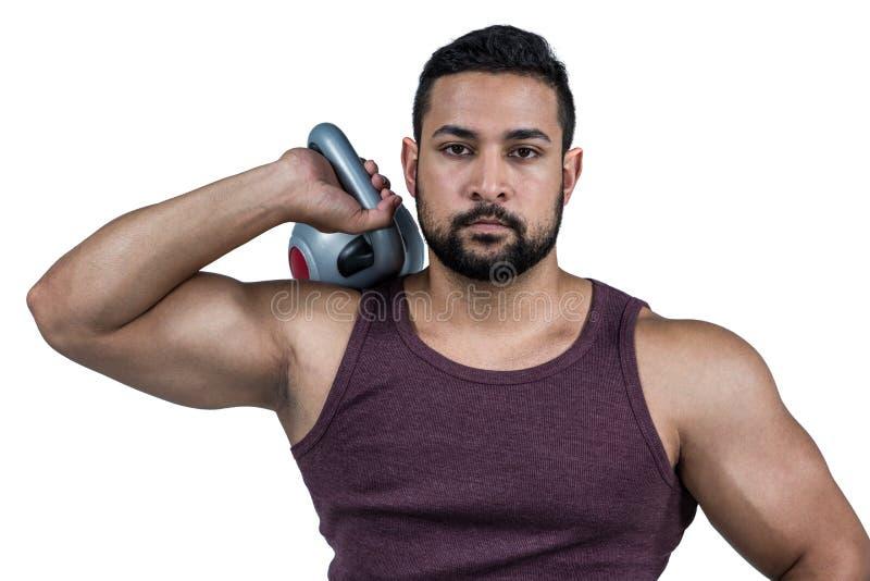 Hombre serio muscular que lleva a cabo un kettlebell fotos de archivo