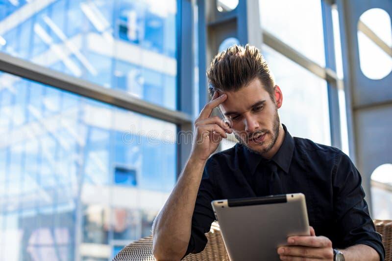 Hombre serio pensativo en línea que aprende vía la almohadilla táctil, sentándose en interior de la oficina imagenes de archivo