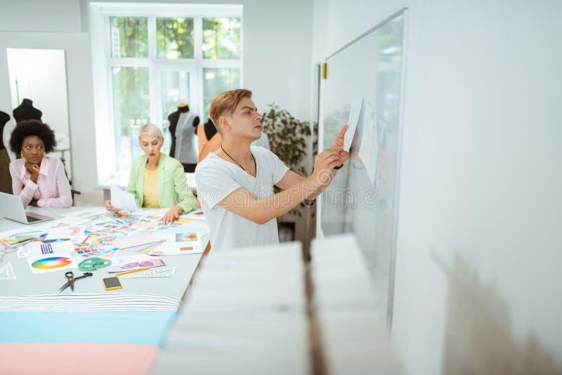 Hombre serio que fija un bosquejo en el whiteboard imágenes de archivo libres de regalías