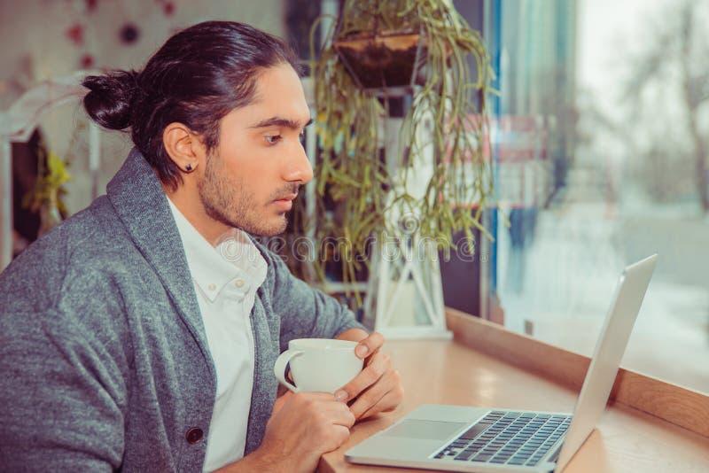 Hombre serio que mira el ordenador portátil mientras que bebe su café o té imagen de archivo libre de regalías