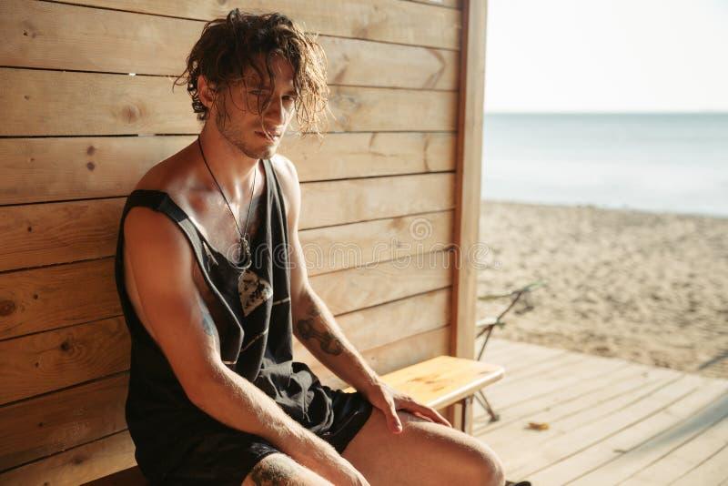 Hombre serio que se sienta en la cabaña de la playa fotos de archivo