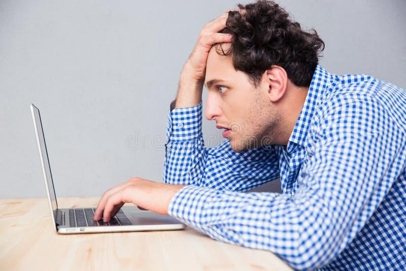 Hombre serio que se sienta en la tabla y que usa el ordenador portátil imágenes de archivo libres de regalías