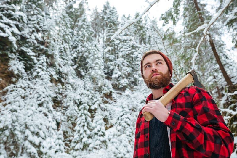 Hombre serio que sostiene el hacha y que camina en bosque del invierno imagen de archivo