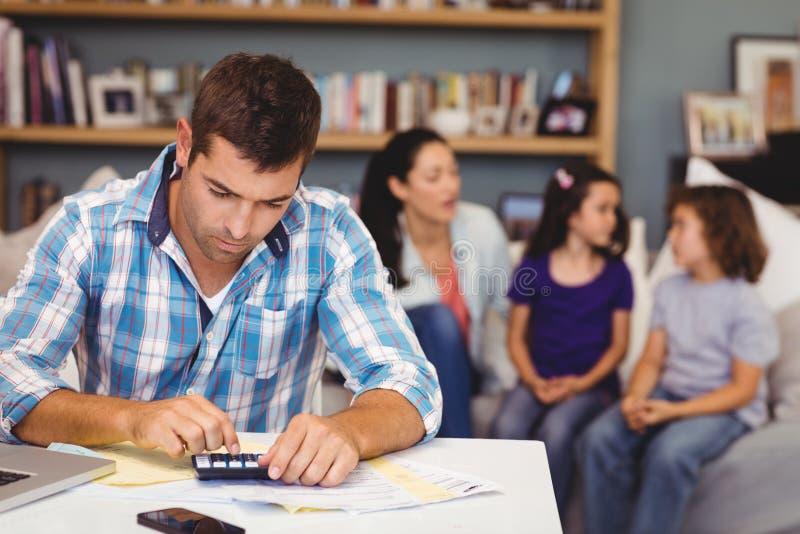 Hombre serio que usa la calculadora mientras que familia que se sienta en fondo imágenes de archivo libres de regalías