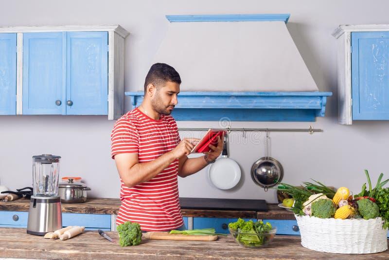 Hombre serio y atento en la camiseta desplazando la tableta buscando la receta en internet para cocinar ensalada, comida vegana imagenes de archivo