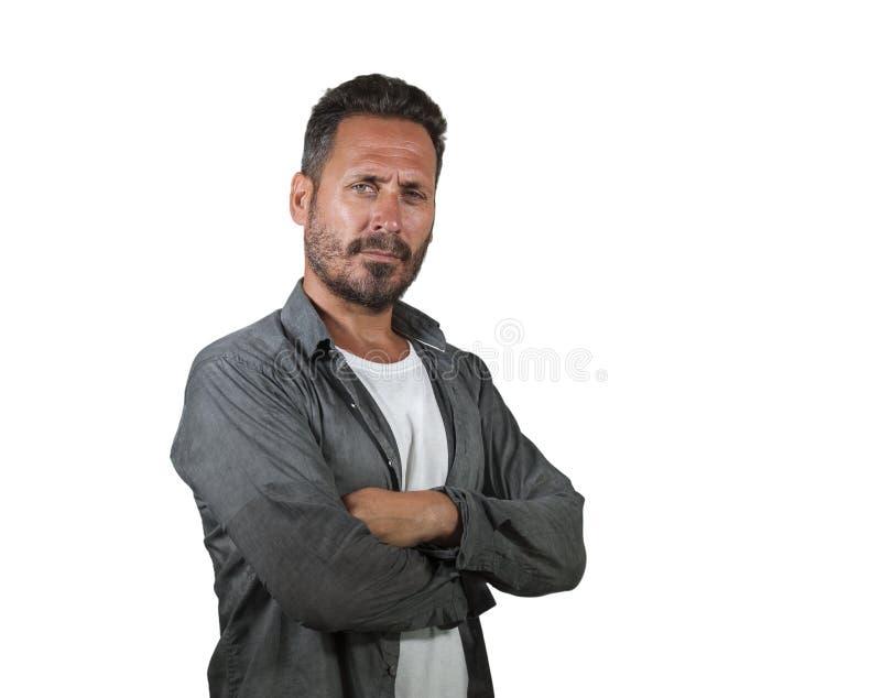 Hombre serio y atractivo en su 40s con los brazos doblados que miran a confiado sonriente de la cámara aislado en la sensación bl foto de archivo libre de regalías
