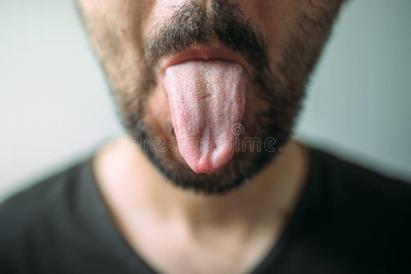 Hombre sin afeitar adulto que pega la lengua hacia fuera imagen de archivo