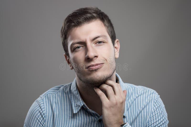 Hombre sin afeitar joven que rasguña la barba que pica con la expresión dolorosa fotografía de archivo libre de regalías