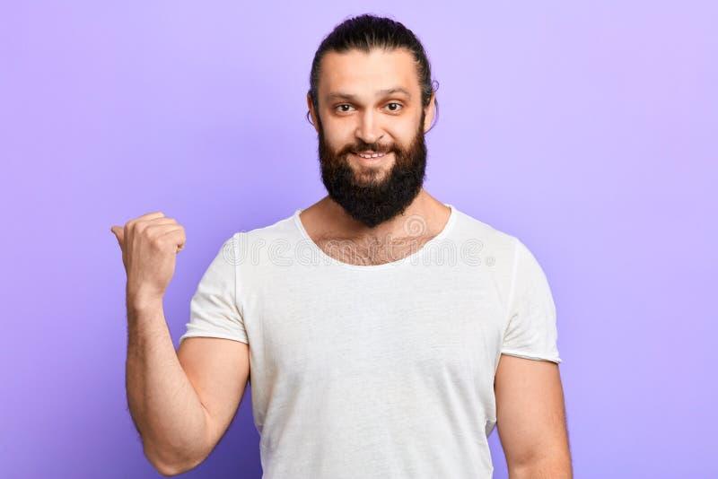 Hombre sin afeitar sonriente de Cheeful que mira y que señala al lado con el pulgar para arriba foto de archivo libre de regalías