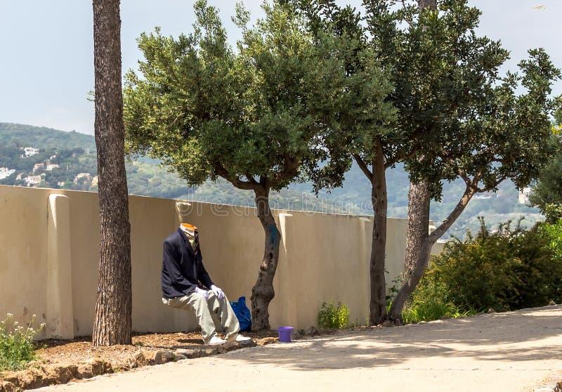 Hombre sin cabeza en el traje que se sienta en el parque Guell fotografía de archivo