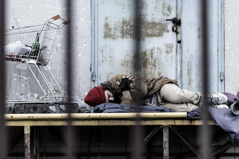 Hombre sin hogar cansado durmiente imagenes de archivo