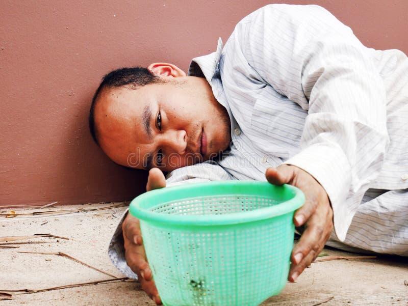 Hombre sin hogar de Asia del primer que se sienta en la calle que camina en el capital imagen de archivo libre de regalías