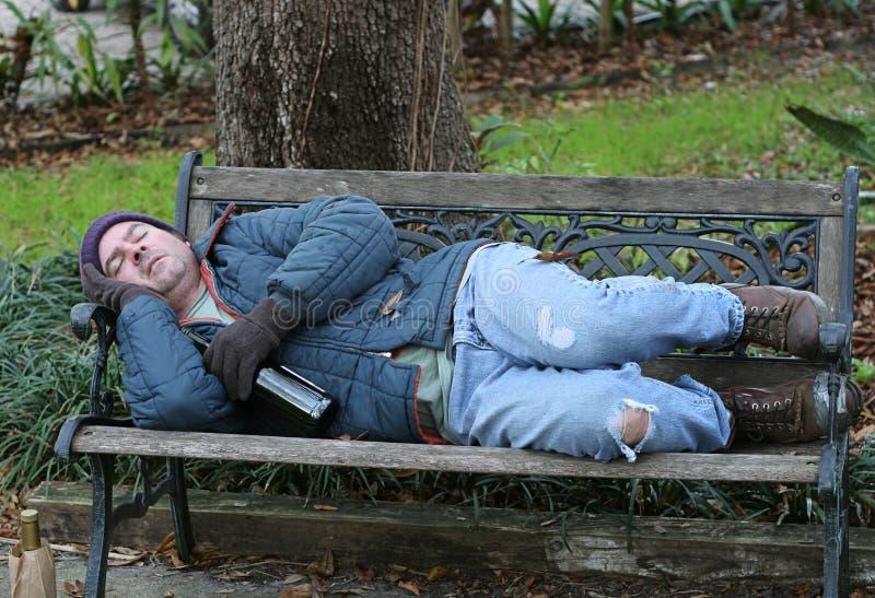 Hombre sin hogar en el banco - a la vista fotografía de archivo
