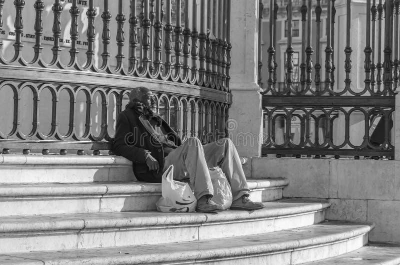 Hombre sin hogar en los pasos del monumento de rey Jose I imagen de archivo libre de regalías