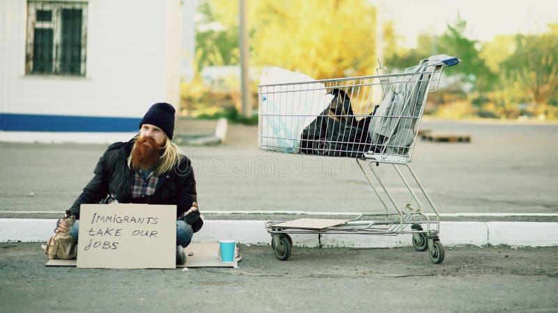 Hombre sin hogar joven del trastorno enojado con la cartulina que se sienta cerca del carro de la compra y del alcohol de la bebi foto de archivo