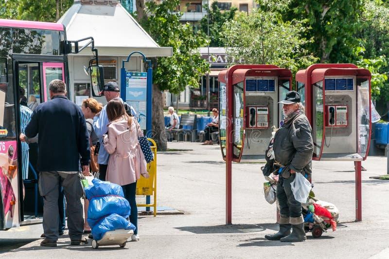 Hombre sin hogar pobre y sucio que coloca en el reloj de la calle a otras personas que entran en el autobús de la ciudad imagen de archivo libre de regalías