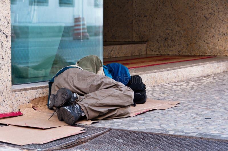 Hombre sin hogar que duerme delante del edificio comercial imágenes de archivo libres de regalías