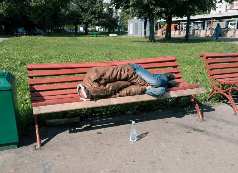 Hombre sin hogar que duerme en el banco imagenes de archivo
