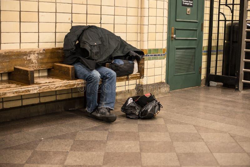 Hombre sin hogar que duerme en el banco en la estación de metro de New York City cubierta por propia capa fotos de archivo libres de regalías