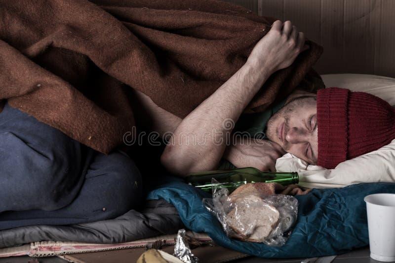 Hombre sin hogar que duerme en la calle imagen de archivo libre de regalías