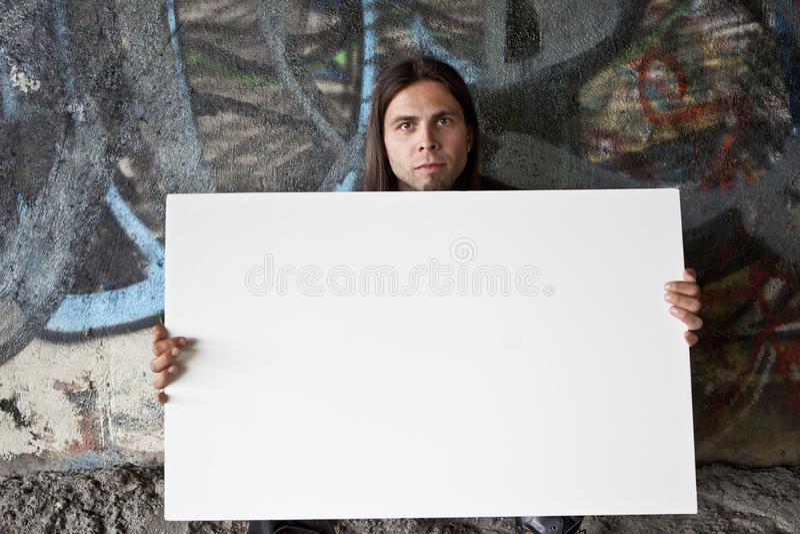 Hombre sin hogar que lleva a cabo una muestra en blanco fotografía de archivo libre de regalías