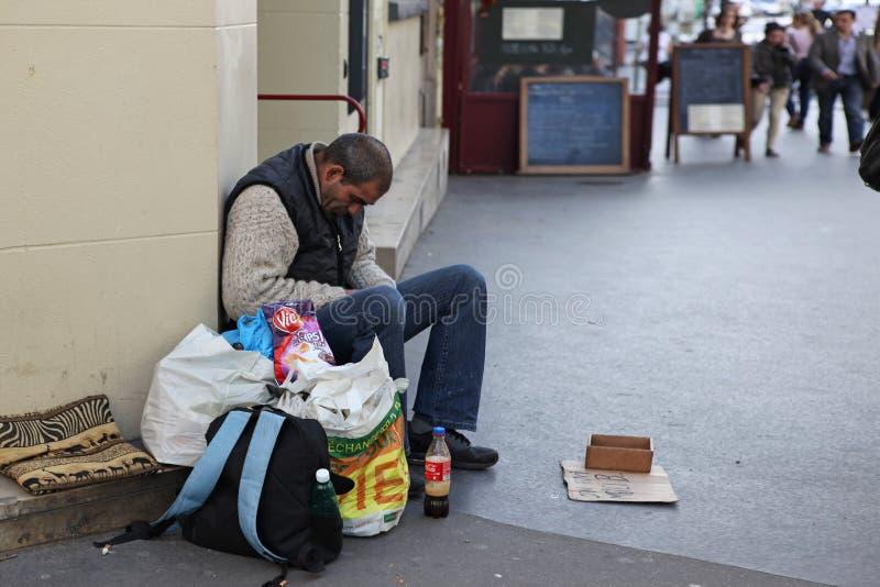 Hombre sin hogar que se sienta en la calle y pedir fotos de archivo