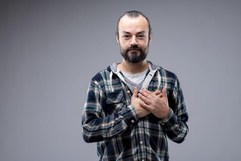 Hombre sincero que cruza sus manos sobre su corazón imágenes de archivo libres de regalías