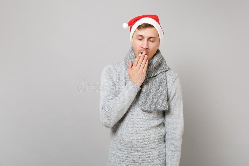 Hombre soñoliento de Papá Noel en el bostezo gris del sombrero de la Navidad de la bufanda del suéter, cubriendo la boca con la e fotos de archivo libres de regalías