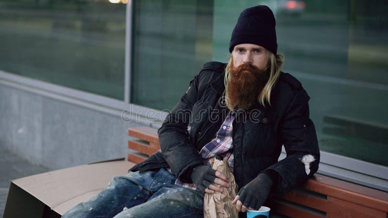 Hombre soñoliento sin hogar borracho que sonríe y que mira la cámara mientras que se sienta en banco la acera foto de archivo