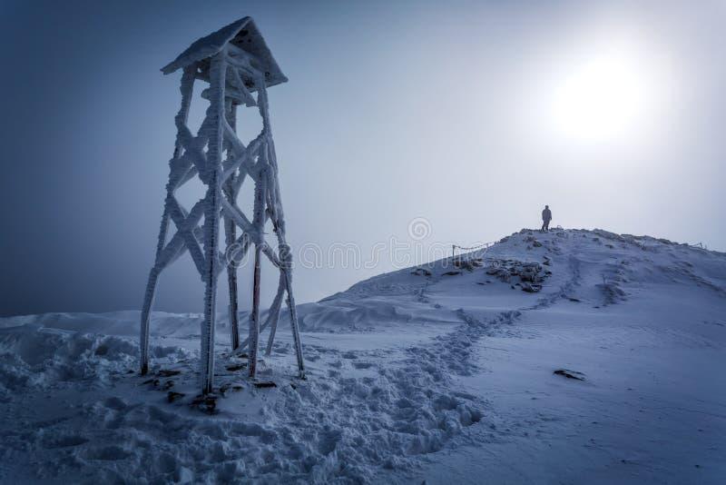 Hombre solitario en el top de la montaña en invierno fotografía de archivo libre de regalías