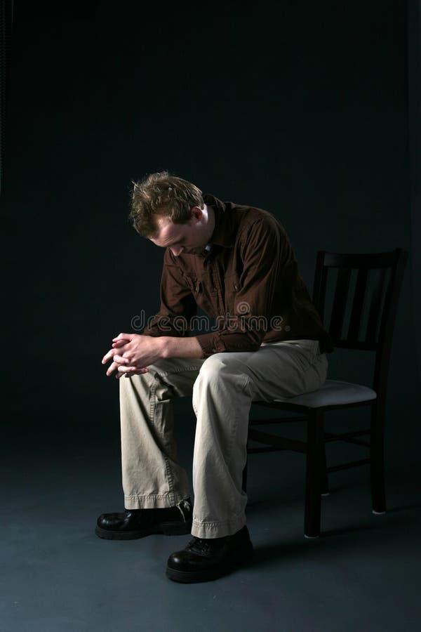 Hombre solitario que se sienta en silla con la pista abajo imagenes de archivo