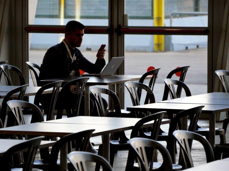 Hombre solo que se sienta en la tabla de la barra que trabaja en figura no reconocible de la silueta del smartphone y del ordenad foto de archivo