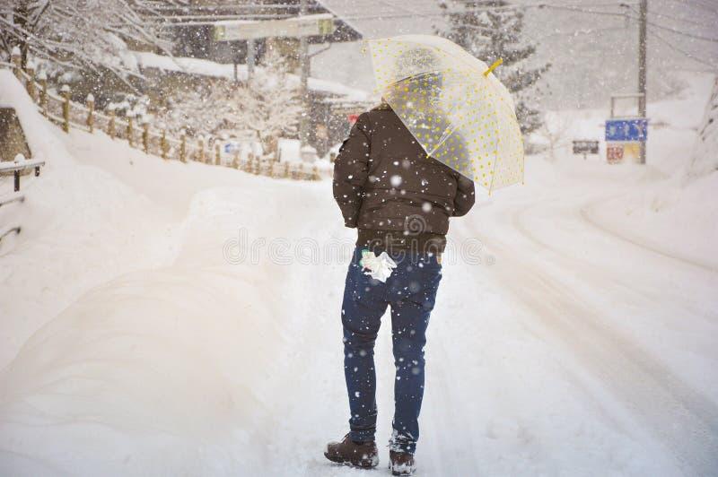 Hombre solo que sostiene el paraguas con caer de la nieve fotos de archivo